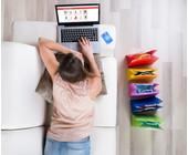 Frau liegt auf dem Sofa und surft im Webshop